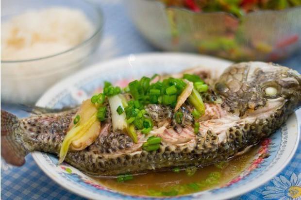 刮去鱼鳞,除去内脏,洗净后,擦干其水分,用刀于鱼身两侧分别3度划口   取葱半棵,一切为二,敲拍之,余下半棵切粒   将敲拍了的两节葱置于一耐热容器上,搁放姜片。然后,置鱼于其上。放调拌好的调味料于鱼身,添水2汤匙,盖上耐热盖(或覆上保鲜纸)   把鱼移到盛茶盘中,然后,在鱼的清蒸汁液中加油1汤匙,再将其汁液均匀地浇于鱼身。最后,撒上葱粒和香菜即可